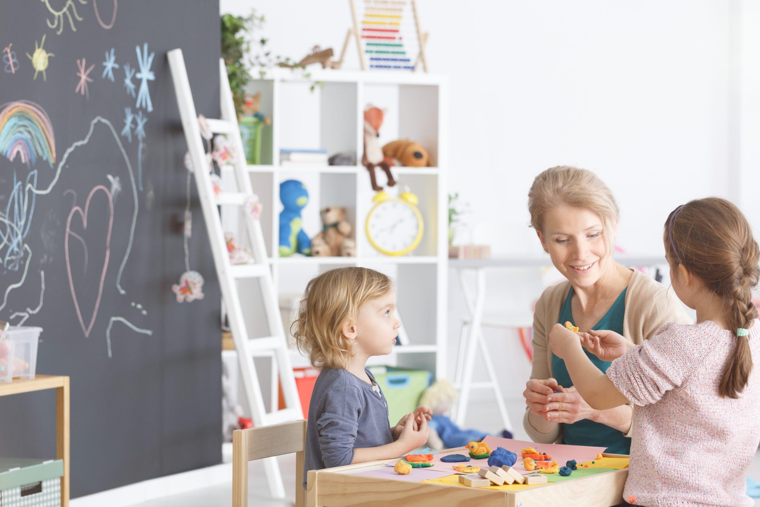Preschool children in kindergarten sticking with plasticine on classes